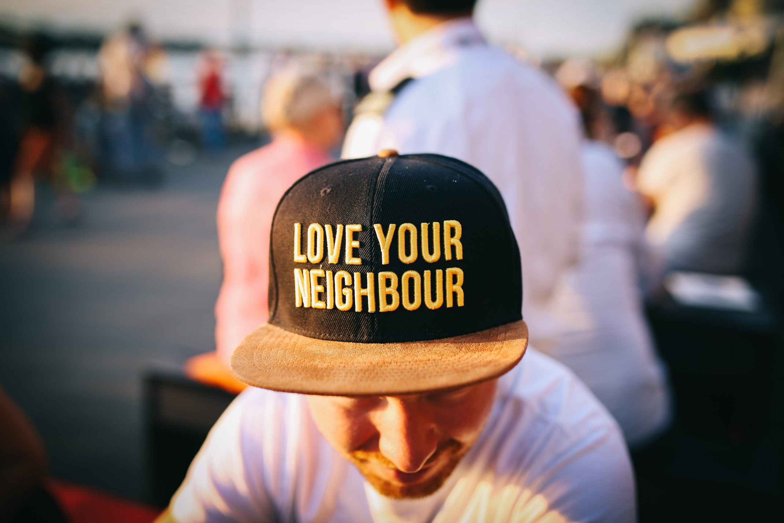 """man with a """"love you neighbor"""" hat"""